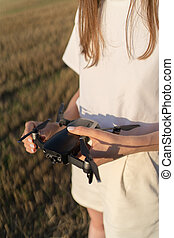 A beautiful girl folds a drone and puts it on her hand. Technological gadget in women's hands at sunset against the sky