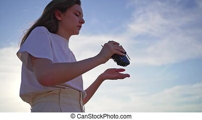 A beautiful girl folds a drone and puts it on her hand. Technological gadget in women's hands at sunset against the sky.