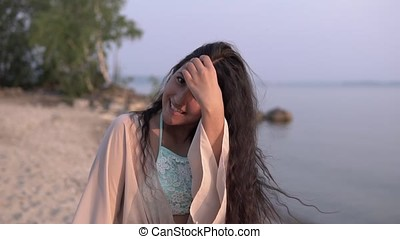 A beautiful girl in a beach tunic turns around herself and smiles. slow motion.