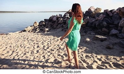 A beautiful girl in a green dress is walking along the coast.