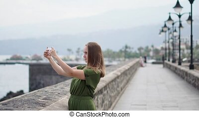 A beautiful girl in a green dress shoots a video for a blog on a mobile phone standing on the waterfront near the ocean and smiling