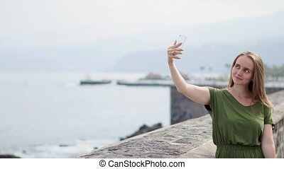A beautiful girl in a green dress takes a selfie on a mobile phone standing on the waterfront near the ocean and smiles