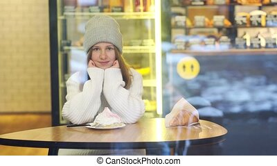 A beautiful teenage girl in a gray hat sits at a table in a confectionery cafe behind glass and looks at passing people. rest from the hustle and bustle. Lunch. Walks in the winter city on vacation