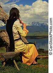 A beautiful girl in a historical costume playing her flute in an open landscape with a lake