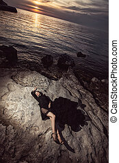 A beautiful girl in a long black dress with open legs lies on rocks, stones on sunset against the background of the sea.