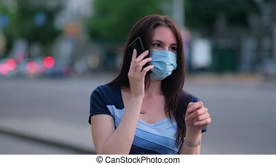 beautiful girl in a mask dials a number and talks on the phone. Quarantine