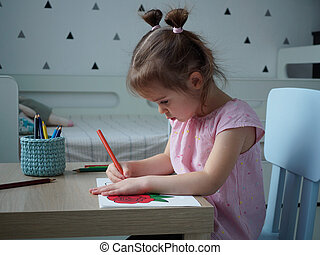 A beautiful girl in a pink striped T-shirt paints a rose with pencils according to the pattern at a wooden table in her room at home