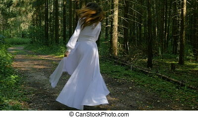 A beautiful girl in a white dress and with long hair dancing in the park. She is happy, laughs, smiles and turns.