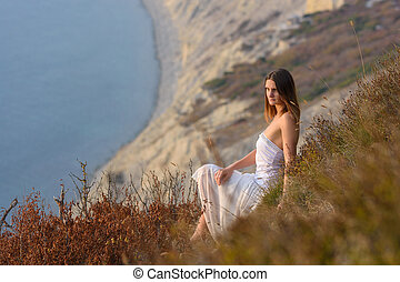 A beautiful girl in a white dress enjoys a beautiful view from the mountain to the sea at sunset