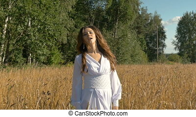 A beautiful girl in a white dress is walking along a field with wheat and singing for joy.