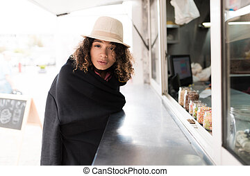 A beautiful girl in a white hat wrapped herself in a black plaid and makes an order in a fast food diner