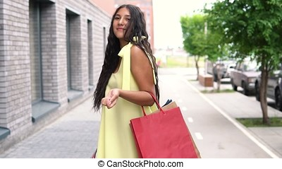 A beautiful girl in a yellow dress is walking down the street after shopping. slow motion.
