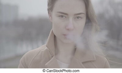 A beautiful girl in park smokes a cigarette