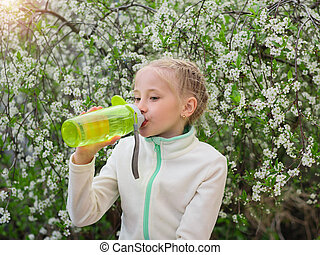 A beautiful girl in the spring Park quenches her thirst with water with lemon and mint.