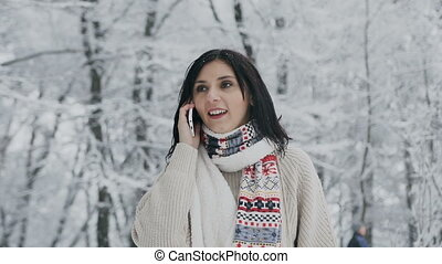 A beautiful girl in the winter forest speaks by phone. Beautiful young brunette uses a smartphone, walking in a snowy park in a fashionable brown sweater, warm scarf and mittens