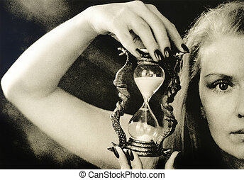 A beautiful girl is holding an hourglass.