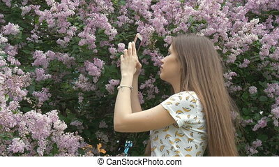 A beautiful girl is taking pictures of a lilac bush. Enjoys beautiful flowers.