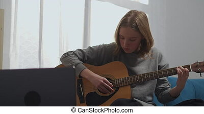 A beautiful girl is watching an online lesson and is engaged in music. Young woman playing guitar at home. An aspiring musician learns to play a musical instrument using a laptop. High quality 4k footage