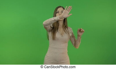 A beautiful girl makes gestures with her hands in front of her. On the green screen.