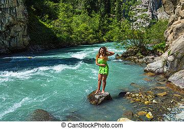 A beautiful girl on the bank of a mountain stream, Kyrgyzstan.