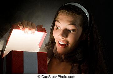 x-mass magic present - a beautiful girl opening x-mass magic...