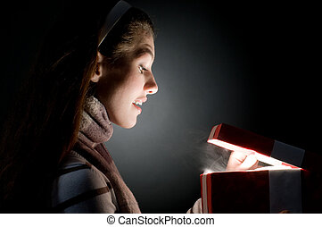a beautiful girl opening x-mass magic present