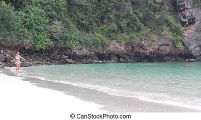 A beautiful girl runs on the beach in her bikini
