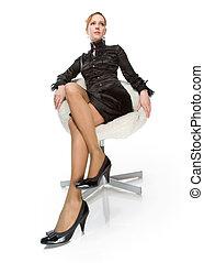 A beautiful girl sitting in an armchair