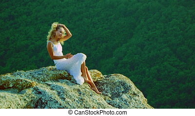 A beautiful girl sitting on a rock