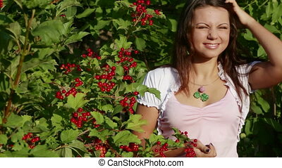A beautiful girl sorts out the berries of viburnum