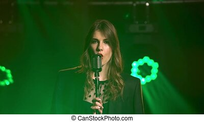 A beautiful girl vocalist sexually singing and gestures with his hands on stage in a vintage microphone. Stylish in a black dress and a men's jacket on the shoulders with red lipstick on the lips. Dark studio with smoke and neon lighting. Dynamic neon lighting effects. Performance vocal and musical ...