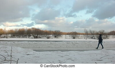 A beautiful girl walks in Park at winter with a backpack. River and clouds in the background.