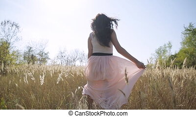 a beautiful girl walks into a field in a skirt slow motion