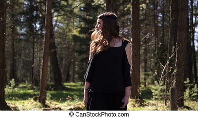 A beautiful girl walks through the woods