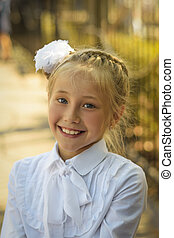 A beautiful girl with a white bow on her head laughs cheerfully before going to school.