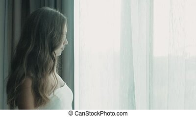 A beautiful girl with long hair in a white suit goes to the window