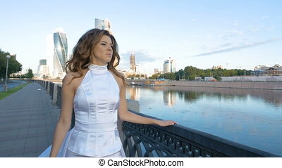 A beautiful girl with long hair in white clothes is walking along the city embankment.