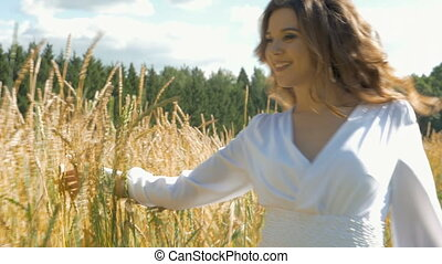 A beautiful girl with long hair is walking along the field with wheat.
