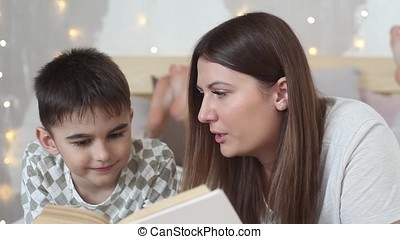 A beautiful girl with long hair reads a book to a small boy lying on a bed and kisses him.HD