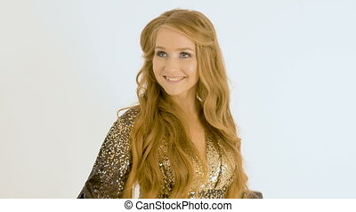 A beautiful girl with long hair. She sings in the studio on a white background.