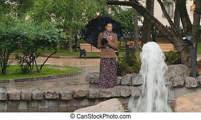 A beautiful girl with sad eyes is standing in the rain in the city park, near the fountain.