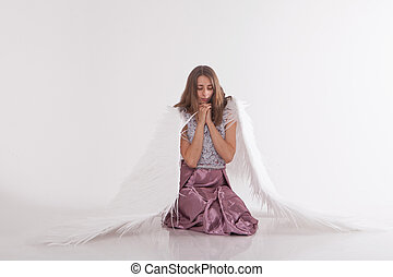 a beautiful girl with white wings is kneeling with her hands folded for prayer. Guardian Angel in pink dress on white background