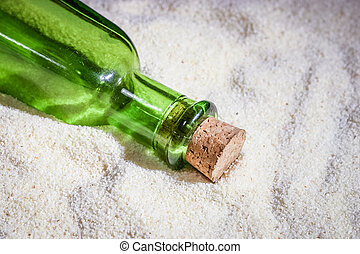A beautiful green bottle in the sand