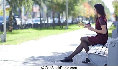 A beautiful happy young girl with an attractive appearance is sitting on a bench in a city park and enjoying the warm autumn weather, drinking coffee
