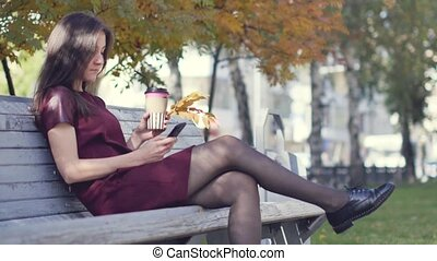 A beautiful happy young girl with an attractive appearance is sitting on a bench in a city park with a phone in her hand and enjoying the warm autumn weather, drinking coffee