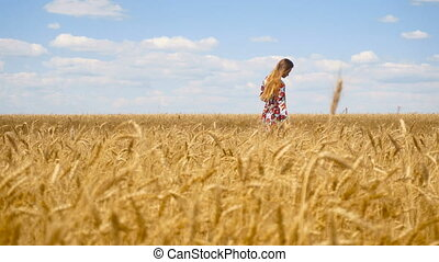 a beautiful lady with long hair goes to wheat field