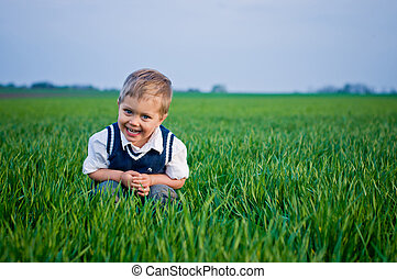 A beautiful little boy sitting in the grass