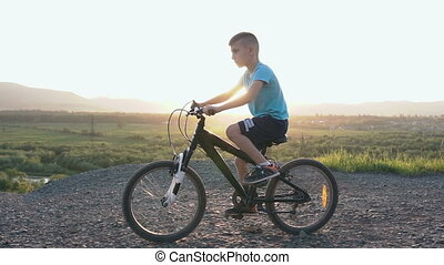 A beautiful little boy who rides a black bike in a mountainous place in the summer in the east or in the sun. The child is cycling on top of a mountain over the river