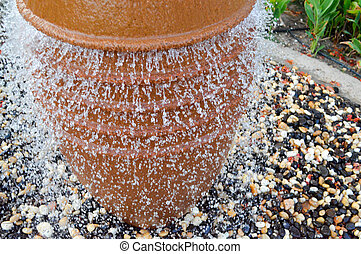 A beautiful little fountain in the form of a brown vase, a jug with falling drops of water on colored stones standing in a flower bed with green plants