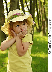 beautiful little girl in a hat on the nature
